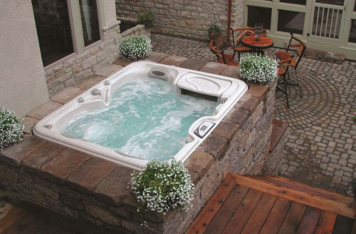 Outdoor hot tub installation surrounded by fall flowers.