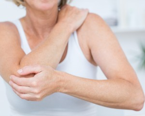 Woman holding her elbow from pain.